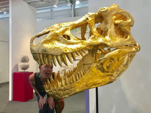 Alisha peeking out from the teeth of a gold plated dinosaur skull